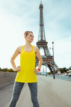 fit sports woman in sport clothes looking into the distance against clear view of the Eiffel Tower in Paris, France.