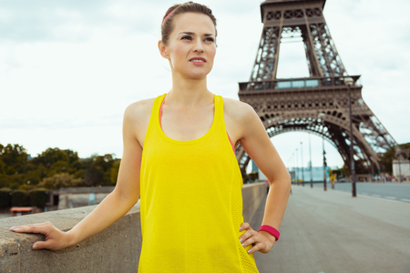 fit woman in fitness clothes not far from Eiffel tower in Paris, France looking into the distance. Stock Photo