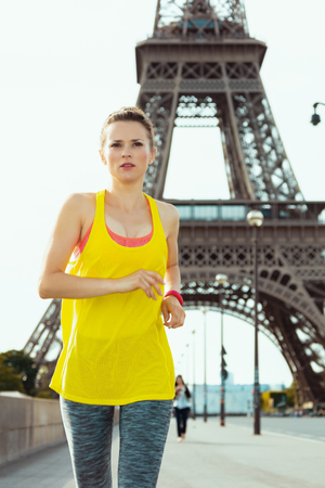 young sports woman in sport clothes running against Eiffel tower in Paris, France.