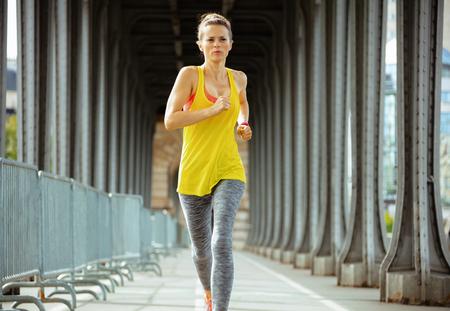 fit woman in fitness clothes on Pont de Bir-Hakeim bridge in Paris running.