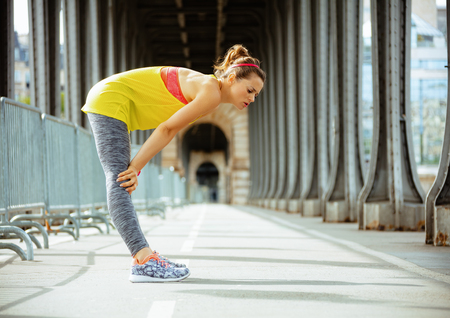 Full length portrait of young sports woman in sport clothes on Pont de Bir-Hakeim bridge in Paris catching breath after exercise. 版權商用圖片