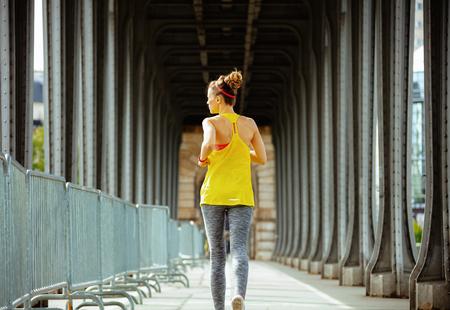 Seen from behind active sports woman in sport clothes on Pont de Bir-Hakeim bridge in Paris running.