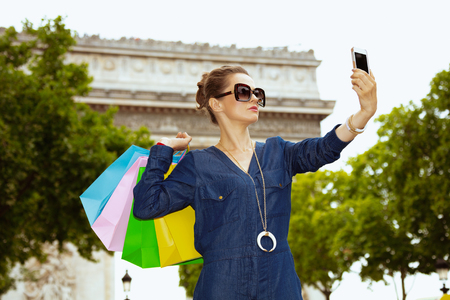 smiling elegant traveller woman in sunglasses with colorful shopping bags taking selfie with smartphone on Champ Elysees in Paris, France.