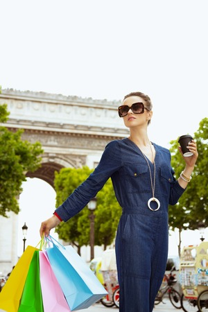 smiling young shopper woman in sunglasses with colorful shopping bags and cup of soy latte looking into the distance in Paris, France. Stock Photo