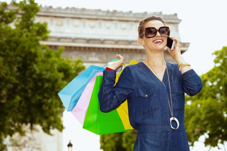 smiling young woman in sunglasses with colorful shopping bags speaking on a smartphone near Arc de Triomphe in Paris, France. Stock Photo