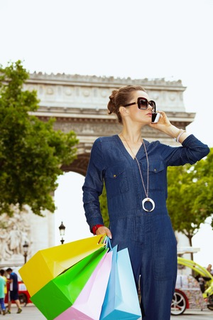 happy young shopper woman in sunglasses with shopping bags using a mobile phone near Arc de Triomphe in Paris, France.