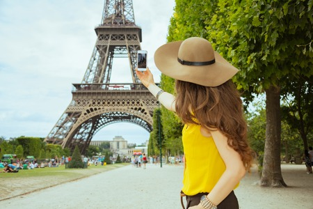Seen from behind young solo tourist woman in yellow blouse and hat taking photo with smartphone against Eiffel tower in Paris, France.