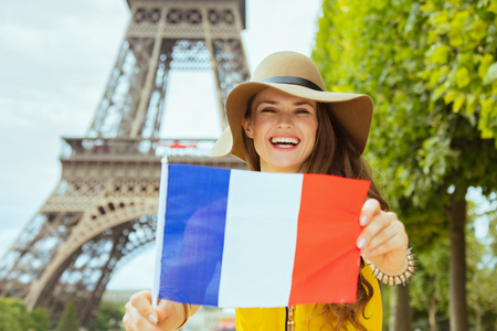 happy young solo traveller woman in yellow blouse and hat showing French flag against clear view of the Eiffel Tower in Paris, France.