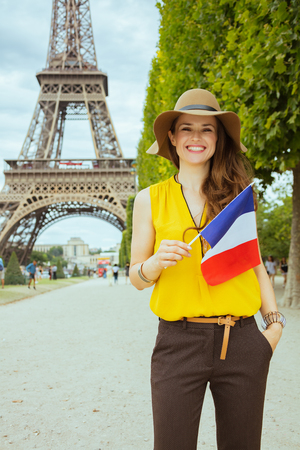 happy modern traveller woman in yellow blouse and hat with French flag at Champ de Mars overlooking Eiffel tower in Paris, France.