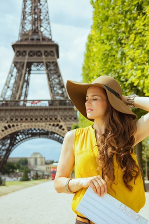 relaxed stylish traveller woman in yellow blouse and hat with map at Champ de Mars overlooking Eiffel tower in Paris, France. Stock Photo
