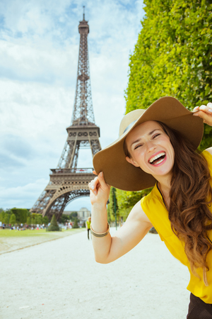 Portrait of cheerful elegant solo traveller woman in yellow blouse and hat against clear view of the Eiffel Tower in Paris, France. Stock Photo