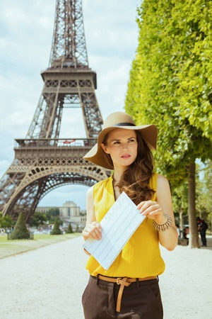 smiling young solo traveller woman in yellow blouse and hat with map against Eiffel tower in Paris, France.