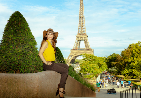 Full length portrait of pensive modern woman in yellow blouse and hat not far from Eiffel tower in Paris, France looking into the distance while sitting at parapet.