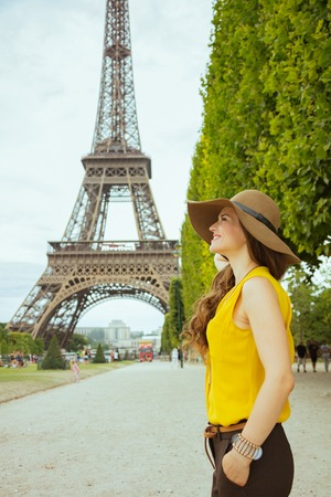 happy modern solo tourist woman in yellow blouse and hat sightseeing against Eiffel tower in Paris, France.
