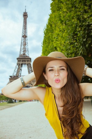 elegant tourist woman in yellow blouse and hat in Paris, France blowing air kiss.