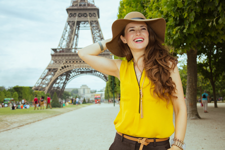 happy modern woman in yellow blouse and hat enjoying promenade against clear view of the Eiffel Tower in Paris, France.
