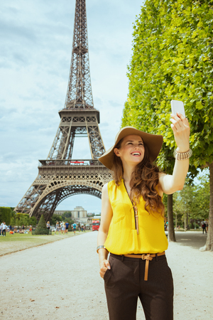 happy modern solo traveller woman in yellow blouse and hat taking selfie with smartphone against Eiffel tower in Paris, France.