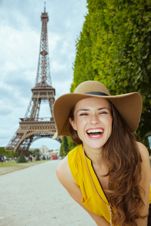 Portrait of happy modern tourist woman in yellow blouse and hat against clear view of the Eiffel Tower in Paris, France.