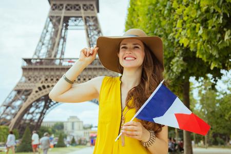 Heureuse femme voyageuse solo élégante en blouse jaune et chapeau avec drapeau français explorant les attractions de Paris, France.