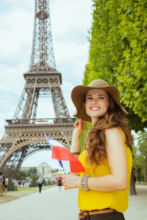 smiling elegant solo traveller woman in yellow blouse and hat with French flag looking into the distance in Paris, France.