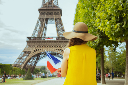 Seen from behind trendy solo traveller woman in yellow blouse and hat with French flag in Paris, France. Stock Photo