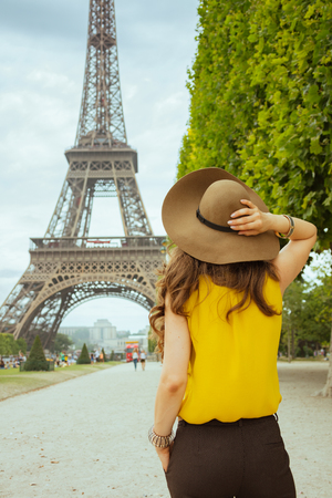 Seen from behind trendy woman in yellow blouse and hat in the front of Eiffel tower in Paris, France having excursion. Stock Photo