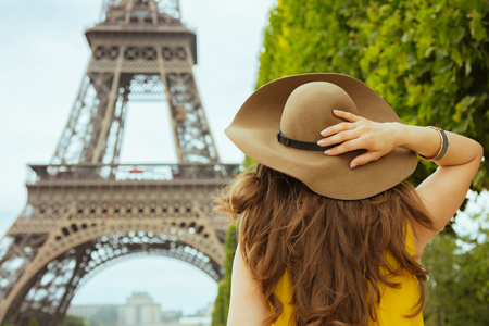 Seen from behind stylish woman in yellow blouse and hat in Paris, France having excursion. Stock Photo
