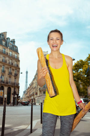 Portrait of cheerful active sports woman in fitness clothes with 2 French baguettes not far from Eiffel tower in Paris, France.