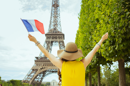 Seen from behind trendy woman in yellow blouse and hat with French flag rejoicing in Paris, France.