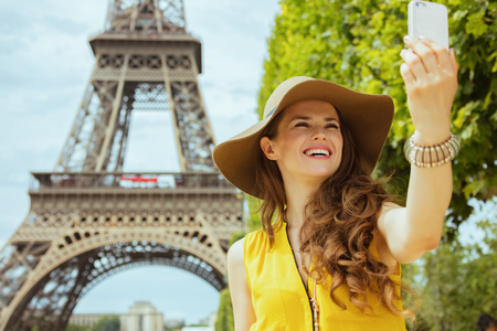 smiling trendy traveller woman in yellow blouse and hat taking selfie with smartphone in the front of Eiffel tower in Paris, France.