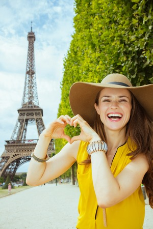 smiling trendy woman in yellow blouse and hat not far from Eiffel tower in Paris, France showing heart shaped hands.