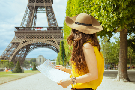Seen from behind elegant traveller woman in yellow blouse and hat with map having excursion against clear view of the Eiffel Tower in Paris, France.