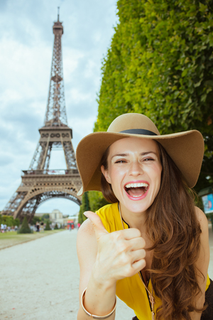 happy young solo tourist woman in yellow blouse and hat in the front of Eiffel tower in Paris, France showing thumbs up.