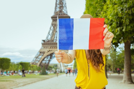 modern solo tourist woman in yellow blouse and hat at Champ de Mars overlooking Eiffel tower in Paris, France showing French flag.