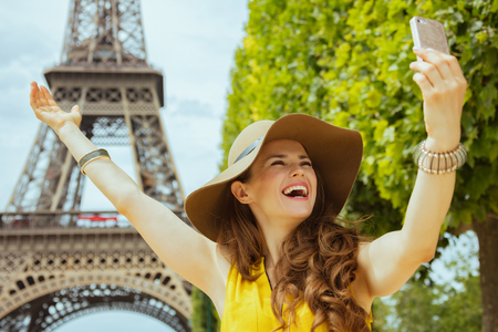 happy trendy traveller woman in yellow blouse and hat rejoicing and taking selfie with cellphone against Eiffel tower in Paris, France.