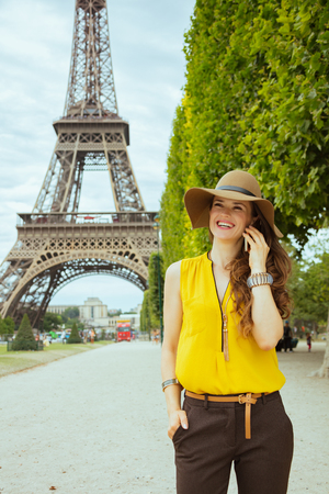 smiling young traveller woman in yellow blouse and hat at Champ de Mars overlooking Eiffel tower in Paris, France speaking on a cell phone.