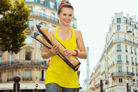 happy young sports woman in fitness clothes with 2 French baguettes crossing street not far from Eiffel tower in Paris, France. Stock Photo