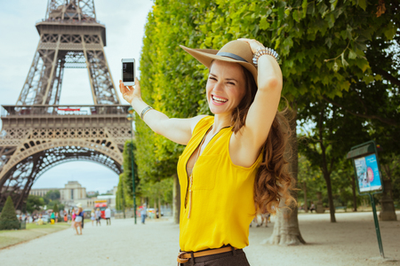 smiling trendy solo traveller woman in yellow blouse and hat taking photo with cellphone in the front of Eiffel tower in Paris, France. Stock Photo