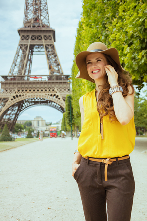 happy young tourist woman in yellow blouse and hat in the front of Eiffel tower in Paris, France talking on a smartphone.