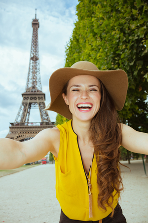 smiling young tourist woman in yellow blouse and hat taking selfie against clear view of the Eiffel Tower in Paris, France.
