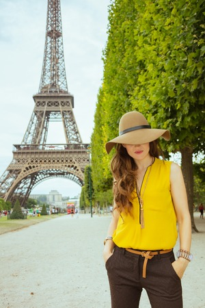 elegant woman in yellow blouse and hat standing not far from Eiffel tower in Paris, France. Stock Photo - 122281568