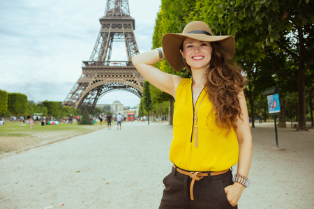 happy modern solo tourist woman in yellow blouse and hat exploring attractions against Eiffel tower in Paris, France.