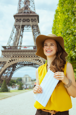 smiling modern traveller woman in yellow blouse and hat with map having excursion against Eiffel tower in Paris, France.
