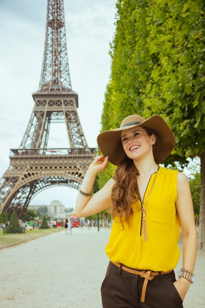 happy trendy tourist woman in yellow blouse and hat at Champ de Mars overlooking Eiffel tower in Paris, France exploring attractions. Stock Photo