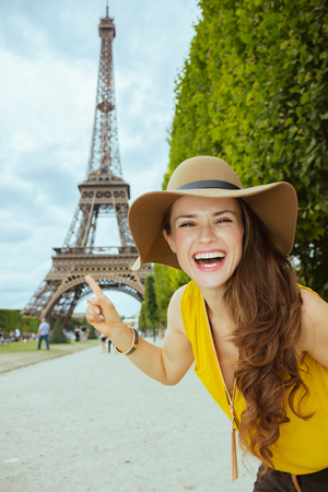 smiling young tourist woman in yellow blouse and hat at Champ de Mars pointing at Eiffel tower in Paris, France