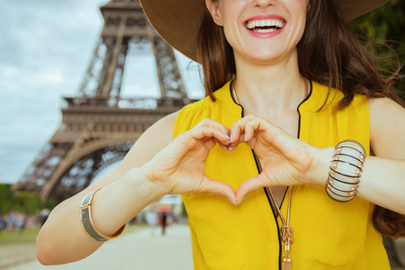 Closeup on happy modern traveller woman in yellow blouse and hat showing heart shaped hands against Eiffel tower in Paris, France. Stock Photo