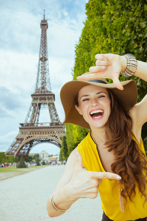 smiling modern woman in yellow blouse and hat framing with hands in the front of Eiffel tower in Paris, France.