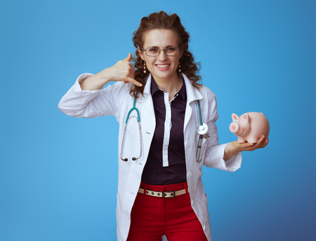 smiling modern medical practitioner woman in bue shirt, red pants and white medical robe with piggy bank showing call me gesture on blue background.