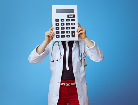 elegant doctor woman in bue shirt, red pants and white medical robe holding big white calculator in the front of face isolated on blue. Stock fotó