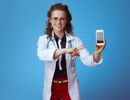 smiling elegant doctor woman in bue shirt, red pants and white medical robe pointing at smartphone isolated on blue background.